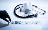 Diagnóza - Parkinsonovou. Lékařská koncepce s tablety, injekce, stetoskop, kardiogram a stříkačky