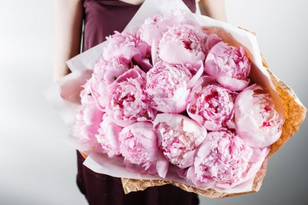 Fresh bright blooming peonies flowers with dew drops on petals. white and pink bud. kraft paper. crisp packaging