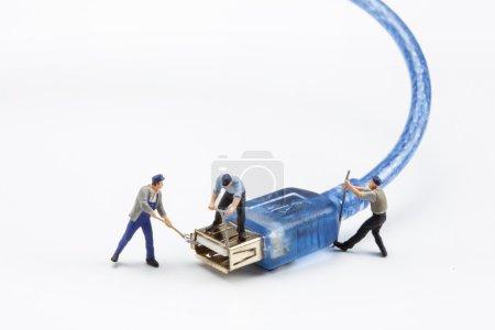 Miniaturmenschen - Arbeiter reparieren einen USB-Stecker
