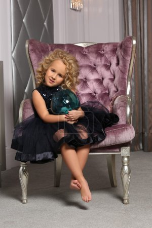 A cute little blond girl  like a doll with curly h...