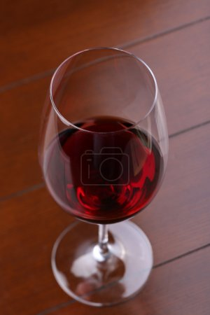 Glass of red wine on wooden table. Close up