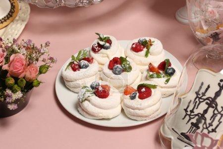 Photo pour Nids de meringue avec crème de fraise et fraises fraîches, framboises, bleuets et une feuille de menthe - image libre de droit
