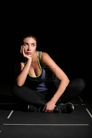 Cute young fitness woman sitting with folded legs