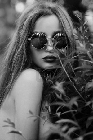 Portrait of brunette girl with blue lips in round sunglasses