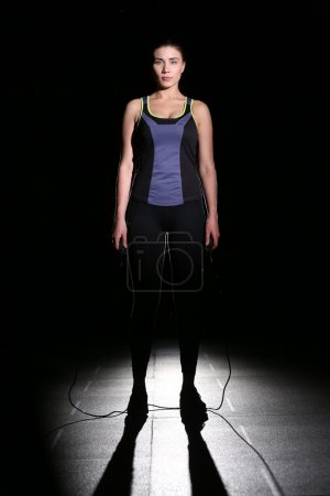 Cute, athletic girl with a skipping rope on black background.