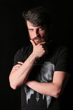 Foto de Bearded guy wearing with serious look holding his chin, beard and mustache, black T-shirt, seriuos look, dark and mysterious, isolated, unshaven, in studio, red-haired man, black background - Imagen libre de derechos