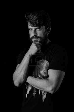 Bearded guy posing and holding hand on his chin. Close.up. Black