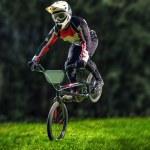 Постер, плакат: Man riding bmx bike performing a trick