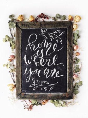 """Foto de La frase """"Hogar es donde estás"""" escrito en el estilo de caligrafía en negro pizarra de madera con rosas amarillas y rosa y hojas verdes - Imagen libre de derechos"""