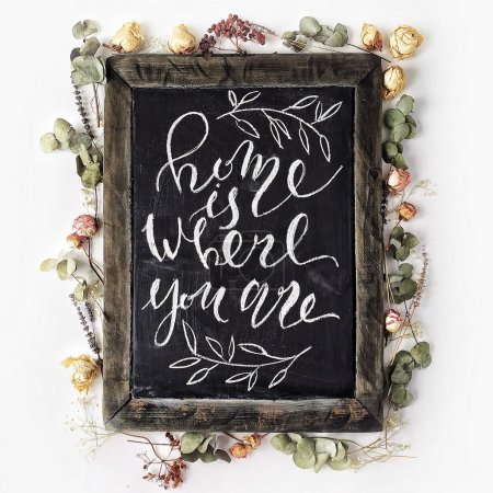 "Phrase ""Home is where you are"" written in calligraphy style at black wooden chalkboard with yellow and pink roses and green leaves"