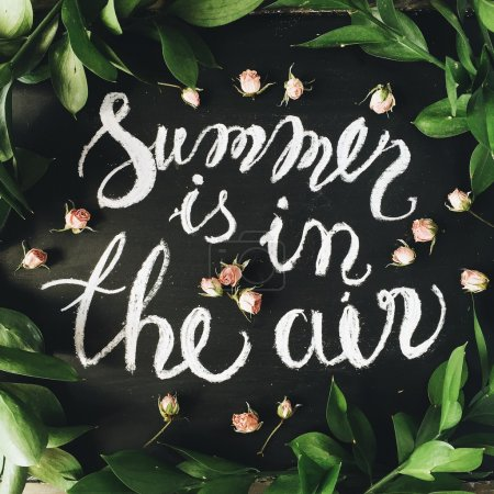 "Phrase ""Summer is in the air"" written in calligraphy style on black chalkboard with pink roses and green leaves. Flat lay"