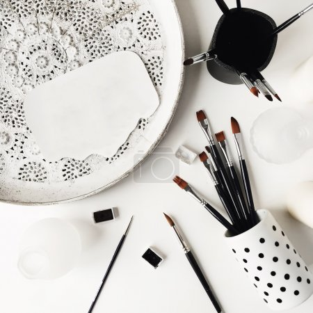 White vintage tray and black watercolor brushes