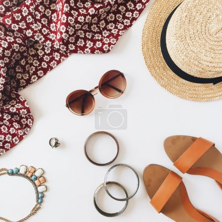 Red dress, straw hat, brown sunglasses, bracelets, shoes and ring isolated on white background