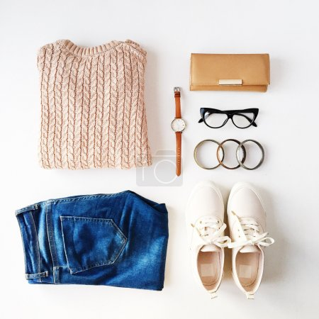 Beige pullover, blue jeans, glasses, bracelets, pink shoes, watch, brown wallet isolated on white background. Overhead view. Flat lay