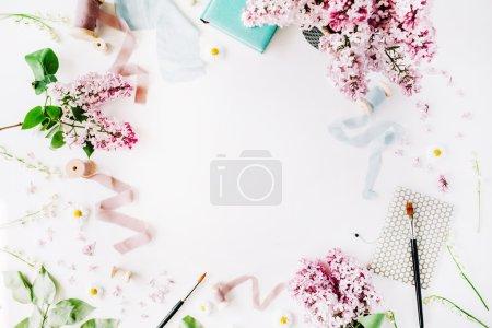 Photo pour Structure florale avec fleurs lilas, camomille, branches fraîches et bobine avec ruban bleu et beige, ordinateur portable isolé sur fond blanc. vue plate Lapointe, top - image libre de droit
