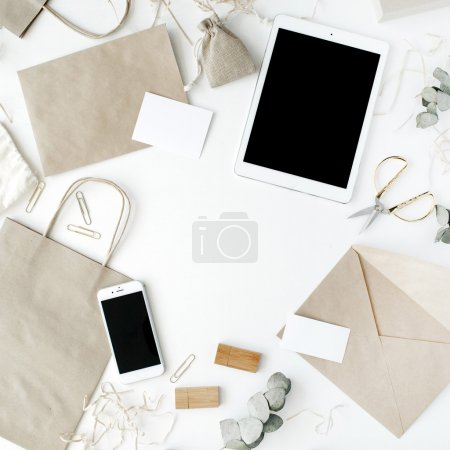 Photo for Desk workspace with tablet, phone, craft envelopes and eucalyptus branches on white background. flat lay, top view - Royalty Free Image