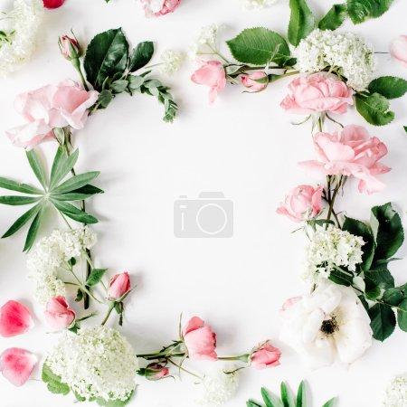 Photo pour Cadre plat laïc avec les roses roses et blanches, les branches, les feuilles et les pétales isolés sur fond blanc. vue de dessus - image libre de droit
