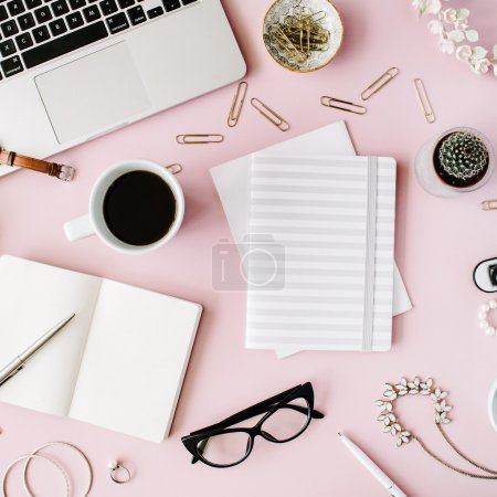 Photo for Flat lay, top view office table desk frame. feminine desk workspace with succulent, laptop, glasses, diary and golden clips on pink background. - Royalty Free Image