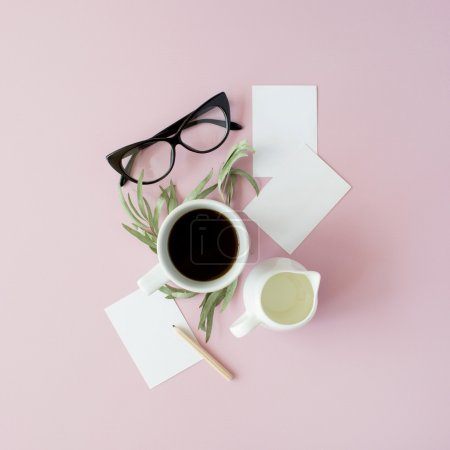 Photo for Cup of coffee, paper notes, pencil, green leaves and glasses on pink background. Flat lay, top view - Royalty Free Image