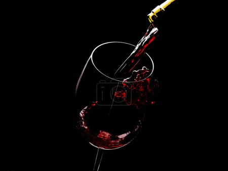 Photo for Pouring red wine into the glass on black background - Royalty Free Image