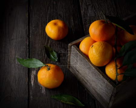 Photo pour Oranges fraîches mûres dans une vieille boîte en bois Sur un fond en bois - image libre de droit