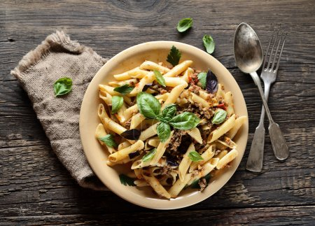 Photo for Pasta with meat and basil on a plate on a wooden background - Royalty Free Image
