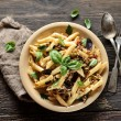 Pasta with meat and basil on a plate on a wooden b...