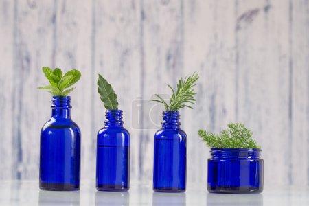 Photo pour Diverses huiles essentielles aromatiques dans les bouteilles bleues - image libre de droit