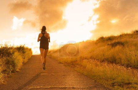 Photo pour Femme courant au coucher du soleil . - image libre de droit