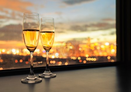 Photo for Two champagne glasses against city background. - Royalty Free Image