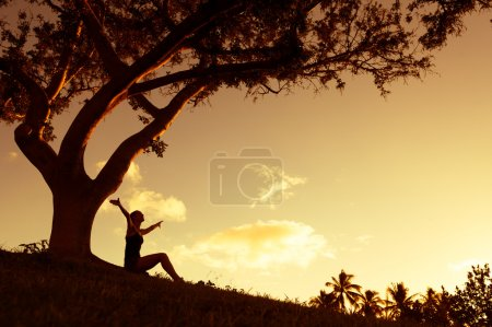 Photo for Silhouette of woman with hands raised into sunset. - Royalty Free Image