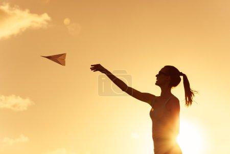 Photo pour Belle silhouette de jeune femme jetant avion en papier . - image libre de droit