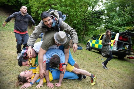 Revelers pile on a competitor at the traditional cheese rolling races on Cooper's Hill