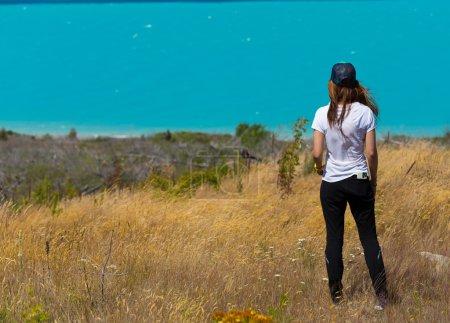 vista posterior de la mujer de pie y mirando hacia fuera hacia la turquesa