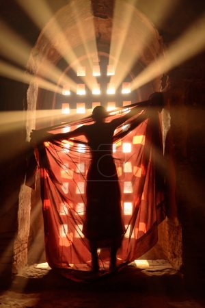 Photo for Novice is dressing in robe in front of stunning light (Blurry, out of focus) - Royalty Free Image