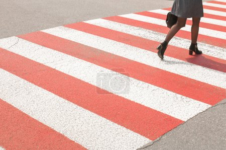 woman on red and white pedestrian crossing, asphalt road, zebra crossing