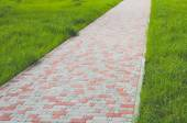 Pathway formed slabs stone between land with fresh green spring or summer grass in a garden park central city town Empty space for full length walking or standing people. The Stone block walk path in the park with green grass background