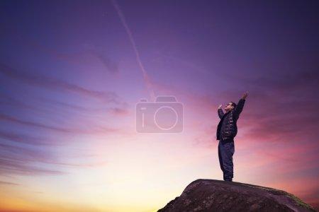 Photo pour Homme avec les mains levées dans le concept du coucher du soleil pour la religion, l'adoration, la prière et la louange - image libre de droit