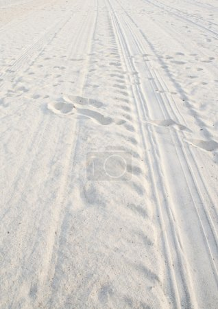White sand with foot print and car tracks...