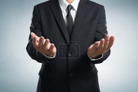 Photo for Businessman in black suit lending a helping hand, isolated on white background - Royalty Free Image