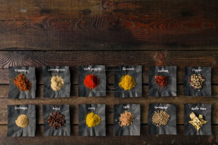 Photo for Colourful spices with names written on paper. Flat lay - Royalty Free Image