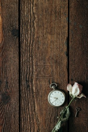 Dry rose on vintage wooden desk. Flat lay. Time concept