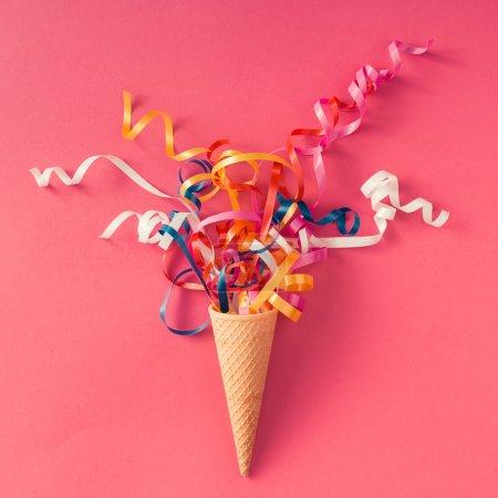 Photo pour Cône de crème glacée avec des banderoles de fête colorées sur fond rose. Pose plate - image libre de droit