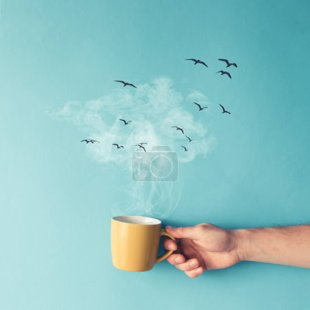 Coffee cup with steam, clouds and birds