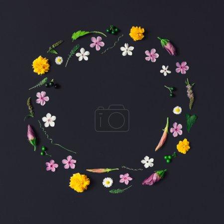 Photo pour Cercle de diverses fleurs sur fond sombre. Poser de plat - image libre de droit