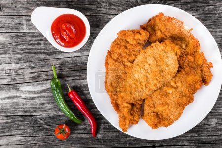 Fried chicken chops on a white dish, top view