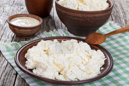 cottage cheese on dish with spoon and cream in bowl