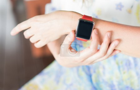 Photo pour Intelligent de l'horlogerie et les femmes des mains. Mettre l'accent sur la montre intelligente. - image libre de droit