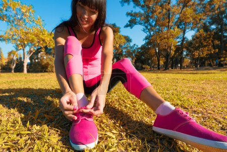 Photo for Running shoes - woman tying shoe laces. Closeup of female sport fitness runner getting ready for jogging outdoors on forest. - Royalty Free Image