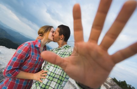 couple kissing on the top of mountain